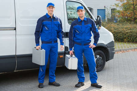 Full length portrait of confident technicians standing against truck on street