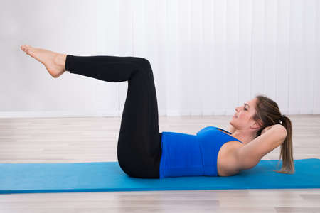 Woman Working Out On Exercise Mat In Yoga Class