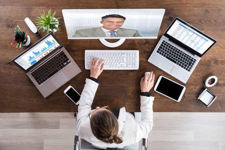 Photo pour Businesswoman Videoconferencing With Senior Colleague On Desktop Computer - image libre de droit