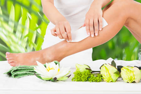 Photo pour Midsection of beautician waxing woman's leg with wax strip at beauty spa - image libre de droit