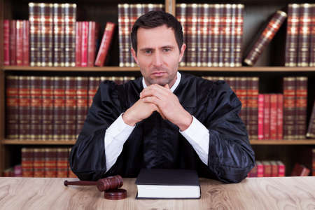 Photo for Portrait of serious judge thinking while sitting at desk in courtroom - Royalty Free Image