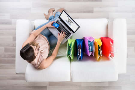 Photo pour High Angle View Of Young Woman Shopping Online With Credit Card On Laptop - image libre de droit