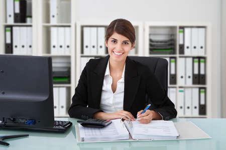 Foto de Portrait of confident female accountant writing on documents at desk in office - Imagen libre de derechos