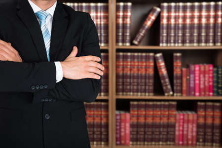 Photo pour Midsection of lawyer with arms crossed standing against books in shelves - image libre de droit