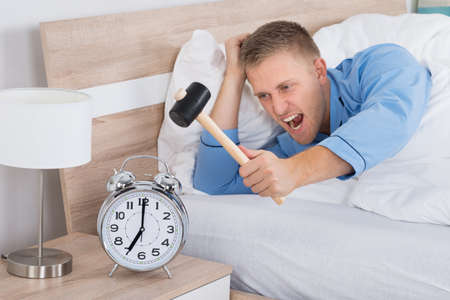 Young Man Smashing Alarm Clock With Hammer On Bed