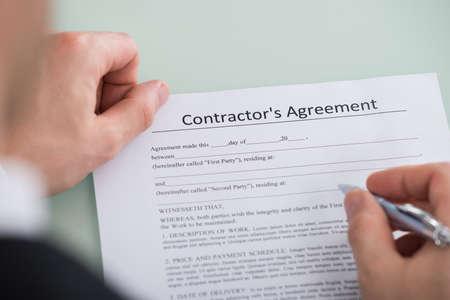 Photo pour Close-up Of Person Hand Over Contractor's Agreement Form - image libre de droit