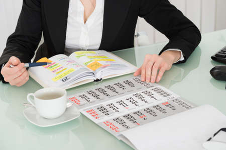 Businesswoman Reading List Of Work In Diary With Calendar On Her Desk