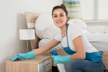 Photo pour Happy Female Housekeeper Cleaning Nightstand In Room - image libre de droit