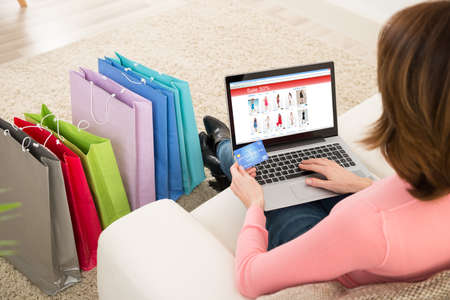 Foto de Young Woman On Sofa Shopping Online With Debit Card - Imagen libre de derechos