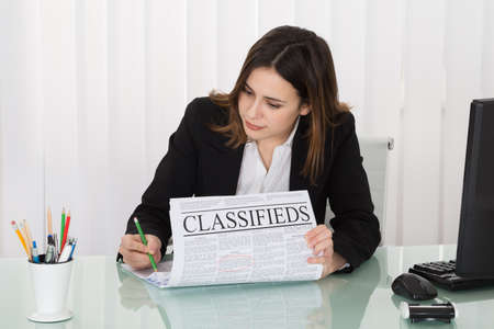 Photo pour Young Businesswoman Highlighting Advertisement On Newspaper In Office - image libre de droit