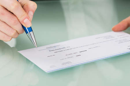 Foto de Close-up Photo Of Businesswoman Hand Signing Cheque - Imagen libre de derechos