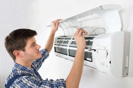 Young Male Technician Cleaning Air Conditioning System At Home
