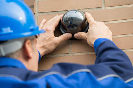Foto de Close-up Of A Mature Male Technician Installing Camera In Building - Imagen libre de derechos