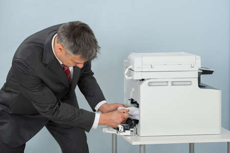 Businessman Bend Down To Remove Paper Stuck In Printer At Office