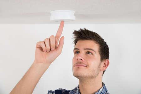Photo pour Young Male Electrician Testing Smoke Detector At Home - image libre de droit