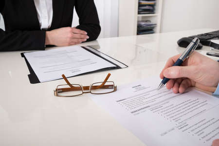 Photo pour Close-up Of Businessperson With Resume And Pen In Office - image libre de droit