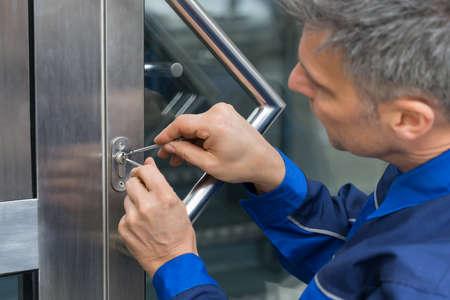 Photo pour Mature Male Lockpicker Fixing Door Handle At Home - image libre de droit