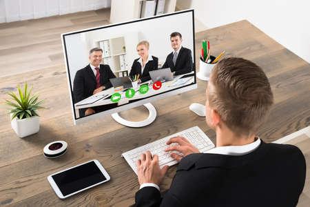 Foto de Young Businessman Attending Videoconference On Computer At Office - Imagen libre de derechos