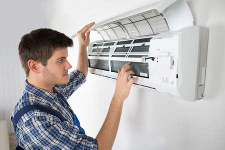 Photo for Photo Of Young Male Technician Repairing Air Conditioner - Royalty Free Image