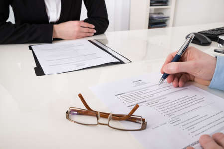 Foto de Close-up Of Businessperson With Resume And Pen In Office - Imagen libre de derechos
