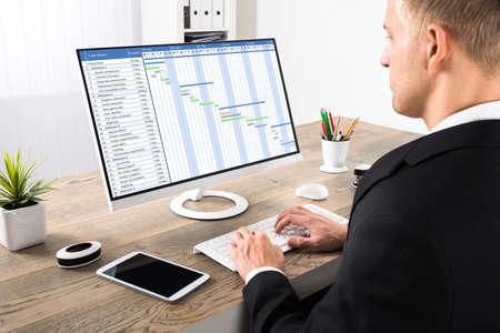 Photo pour Young Businessman Working On Gantt Chart On Computer At Office - image libre de droit