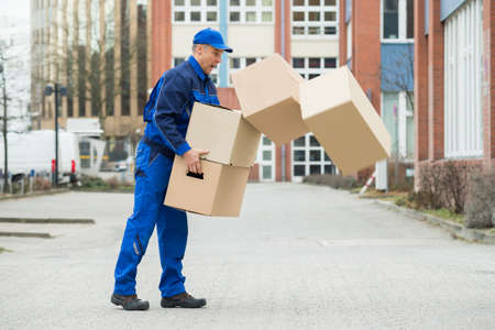 Delivery Man With Falling Stack Of Boxes On Street