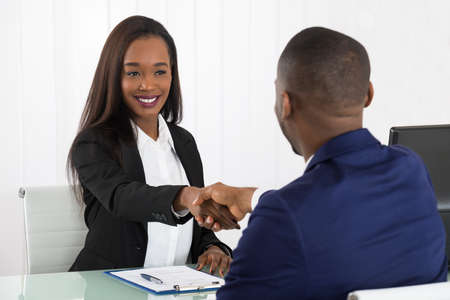 Photo pour Two Successful African American Businesspeople Shaking Hands At Office - image libre de droit