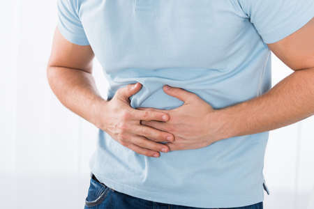 Close-up Of Young Man Suffering From Stomach Ache Standing At Home