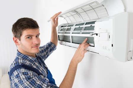 Photo for Young Male Technician Repairing Air Conditioner At Home - Royalty Free Image