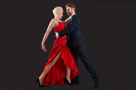 Portrait Of Young Happy Couple Dancing On Black Background