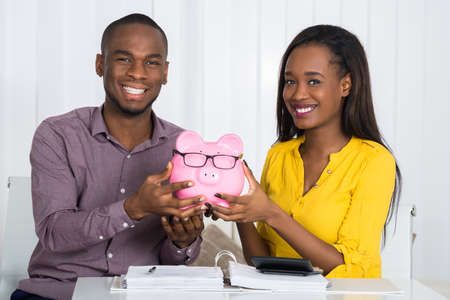 Happy Couple Holding Piggybank With Invoice And Calculator On Desk