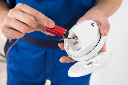 Close-up Of Electrician Hand Holding Battery Of Smoke Detector