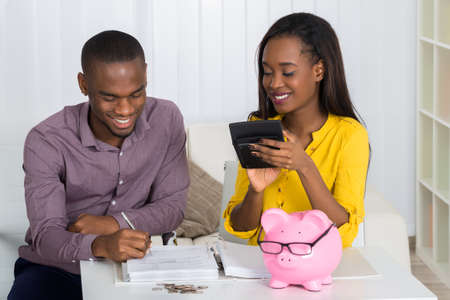 Photo pour Happy Young Couple Calculating Bill With Coins And Piggybank On Desk - image libre de droit