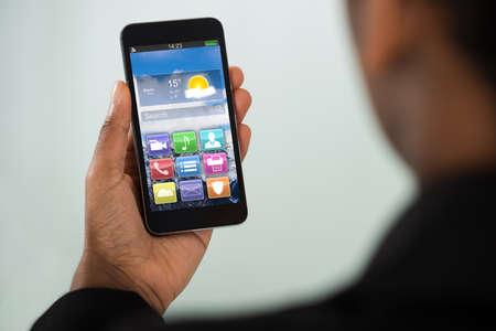 Photo pour Close-up Of Young Businesswoman Holding Mobile Phone With Multicolored App - image libre de droit