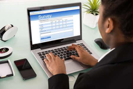 Photo pour Close-up Of A Young African Businesswoman Filling Online Survey Form On Laptop - image libre de droit