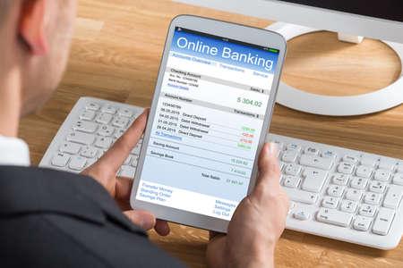 Photo pour Close-up Of Young Businessperson Online Banking Using Digital Tablet At Computer Desk - image libre de droit
