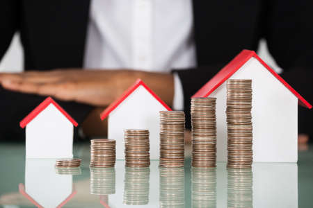 Photo pour Close-up Of Businesswoman With Different Size Of House Model And Stacked Coins On Desk - image libre de droit