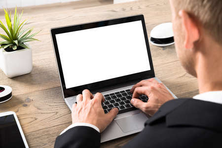 Photo for Close-up Of A Young Businessman Working On Laptop In Office - Royalty Free Image