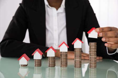 Photo pour Close-up Of Businesswoman Hand Arranging House Model On Stacked Coins At Desk - image libre de droit