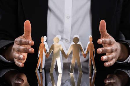Photo pour Close-up Of Businessperson Protecting Cut-out Figures On Desk - image libre de droit