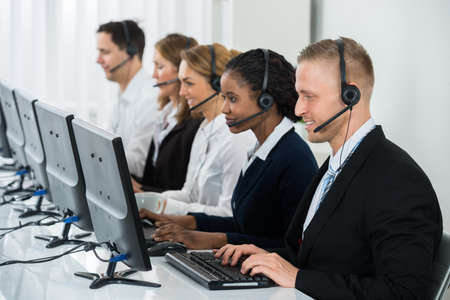 Photo pour Team Of Businesspeople With Headsets Working In Call Center Office - image libre de droit