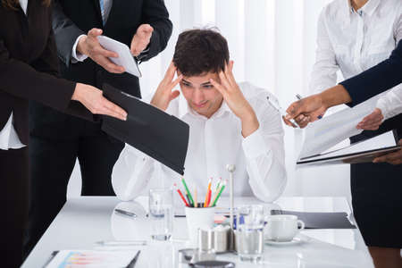 Photo pour Young Businessman Stressed Out At Work Surrounded By Businesspeople - image libre de droit