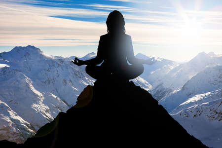 Photo for Silhouette Of A Woman Performing Yoga On Mountain Peak - Royalty Free Image