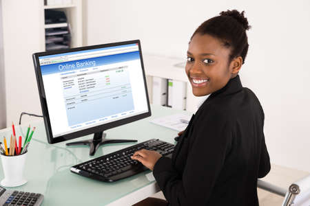Photo pour Young Happy African Businesswoman Doing Online Banking On Computer At Office - image libre de droit