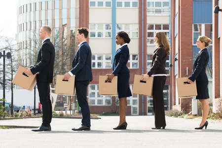 Photo for Group Of Multiracial Businesspeople With Cardboard Boxes Standing In A Line - Royalty Free Image