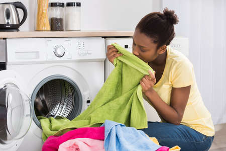 Photo for Young African Woman Smelling Clothes After Washing At Home - Royalty Free Image