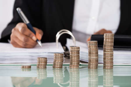 Foto per Close-up Of Businesswoman Calculating Tax With Stack Of Coins On Desk - Immagine Royalty Free