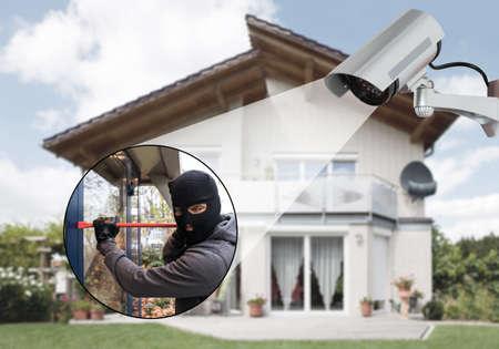 Photo pour Surveillance Camera Capturing Burglar Using Crowbar To Open Glass Door - image libre de droit