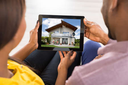 Photo pour Close-up Of A Couple Looking At House On Digital Tablet - image libre de droit
