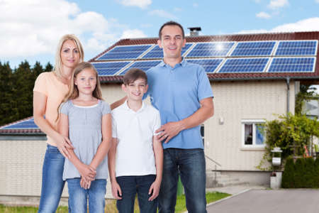 Photo for Portrait Of A Happy Family Standing Outside Their House With Solar Panels On Roof - Royalty Free Image